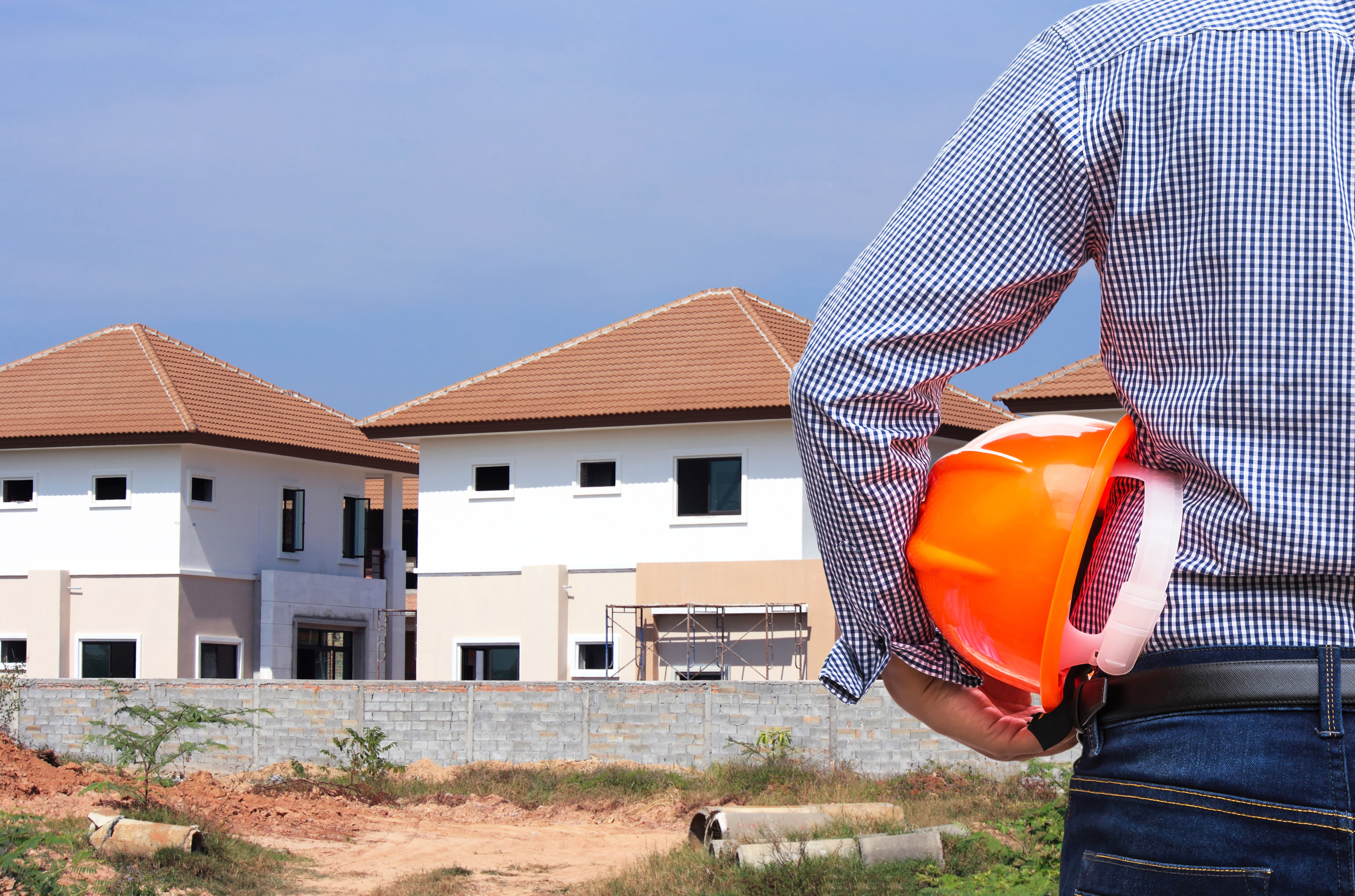 resident engineer holding yellow safety helmet in construction new home housing development background